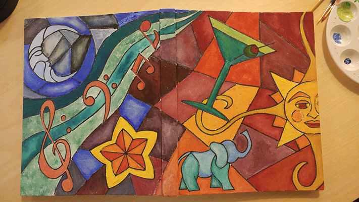 Painted sketchbook cover with stained glass style images of sun, moon, star, martini glass, elephant, and musical notes.